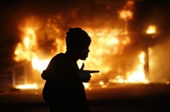 En protestant foran en brennende bygning under en av opptøyene i Ferguson (Reuters)