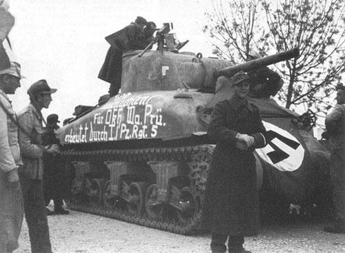En amerikansk Sherman-tank, overtatt av tyske styrker, merket med flagg og håndmalt beskjed på siden.