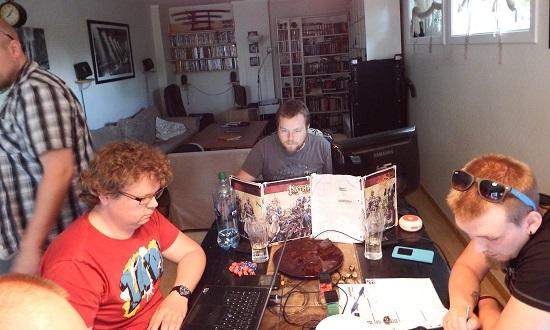 GameMaster i dyp konsentrasjon, mens spillerne fyller opp glass, og sjekker regler på nett.